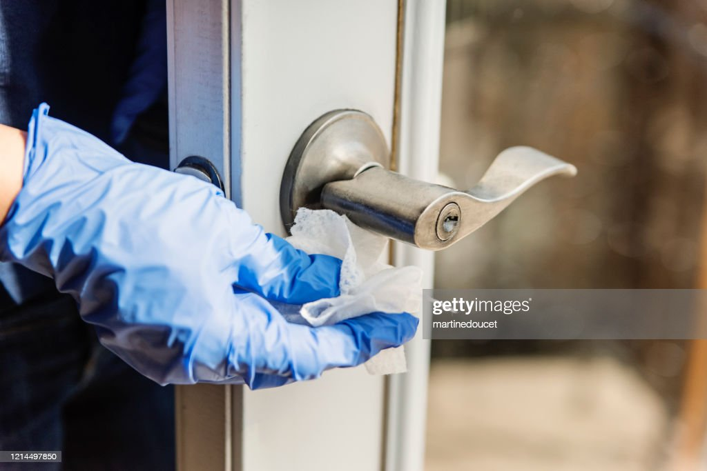 Hand with glove wiping door handle. : Stock Photo