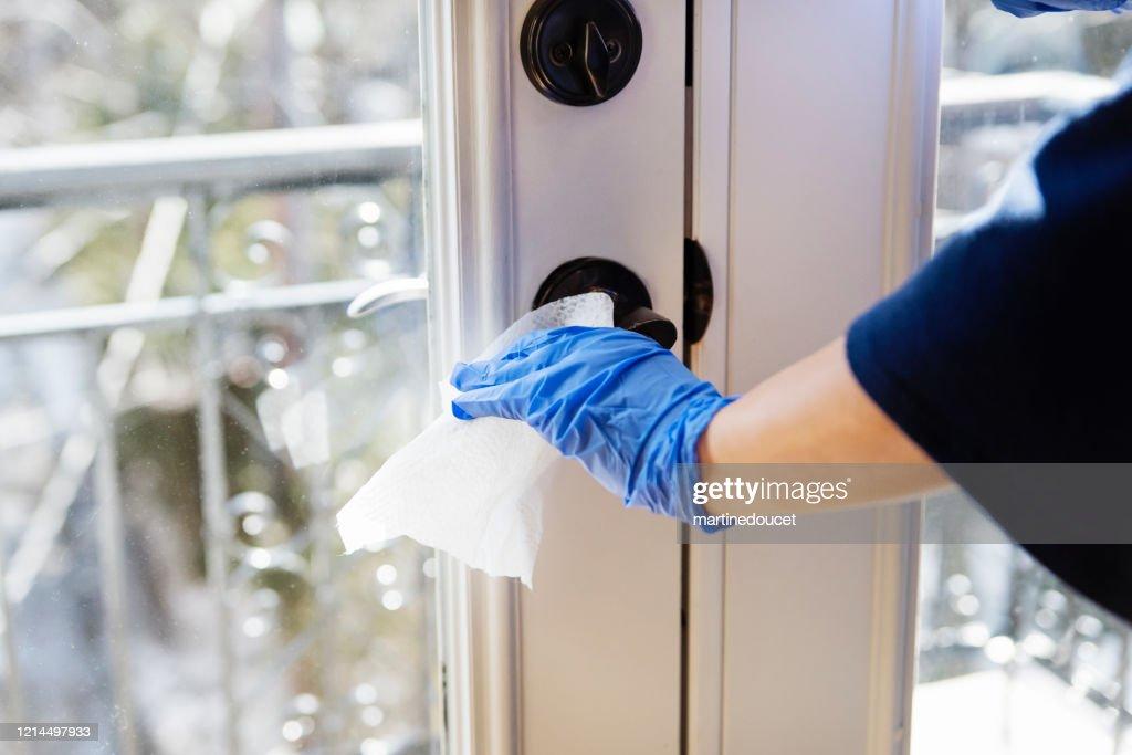 Hand with glove wiping door handle. : Stock Photo