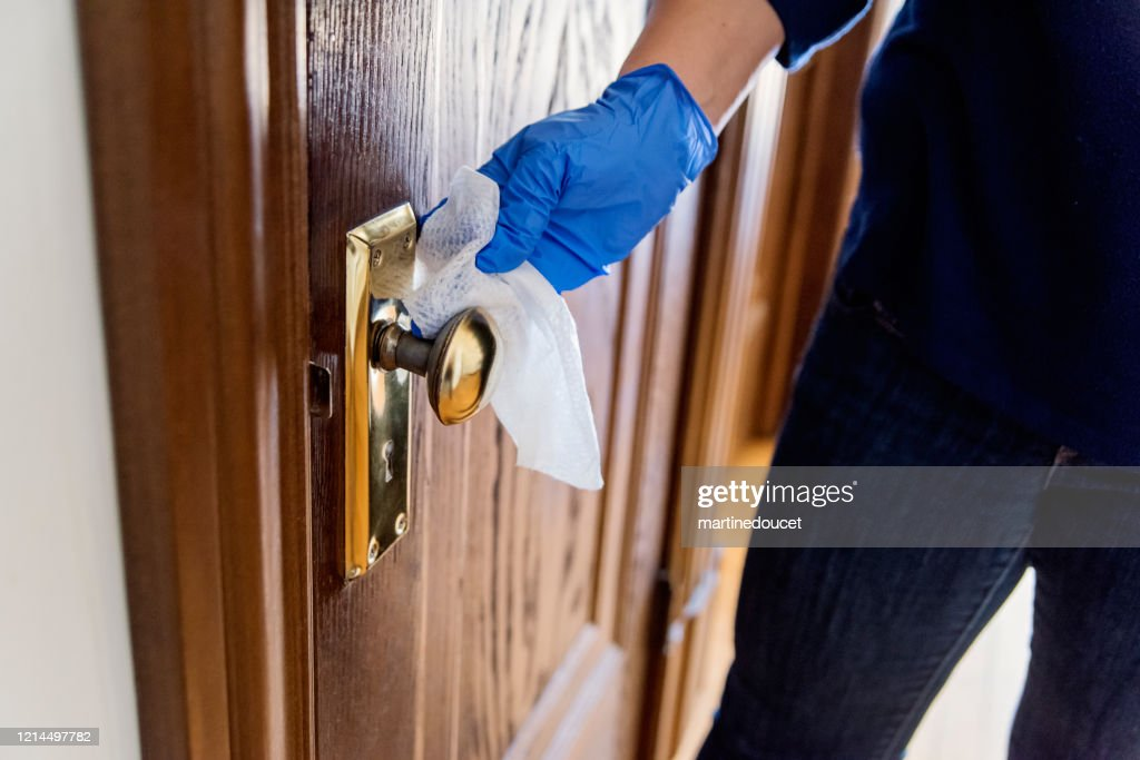 Hand with glove wiping doorknob on wooden door. : Stock Photo