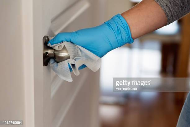 hand with glove wiping doorknob. - handle stock pictures, royalty-free photos & images