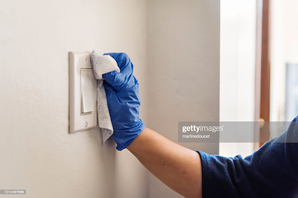 Hand with glove wiping light switch. : Stock Photo