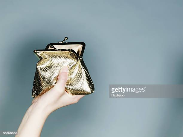 hand with gold purse - gold purse stock pictures, royalty-free photos & images