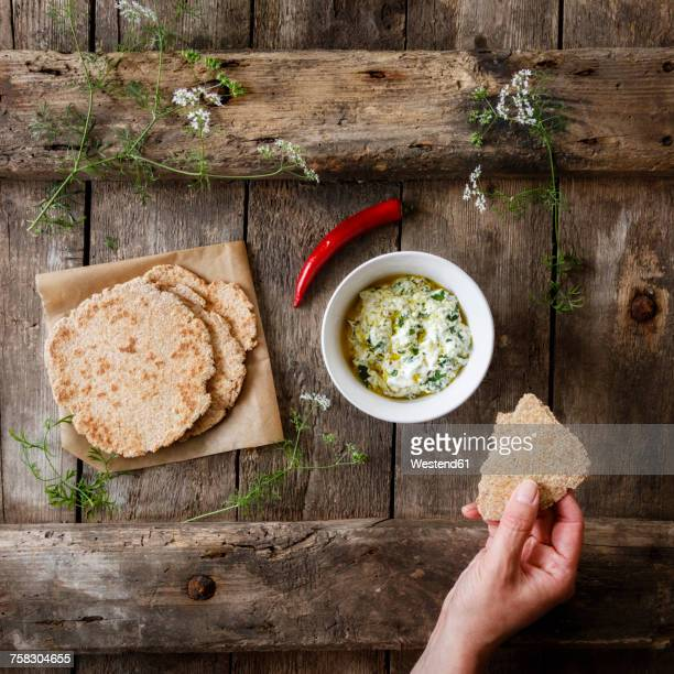 hand with home-baked naan bread and bowl of curd dip - dipping sauce stock pictures, royalty-free photos & images