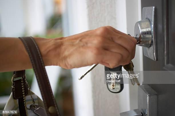 Hand with keys unlocking door