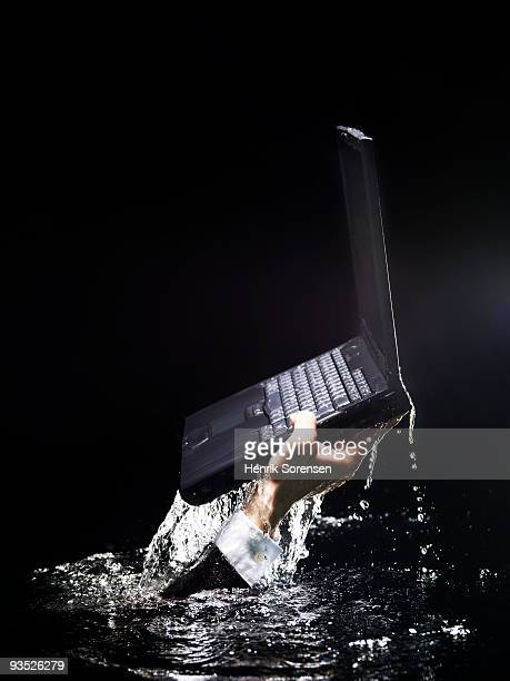 hand with laptop comming up through water