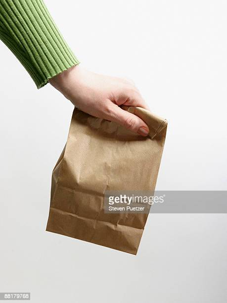 hand with lunch bag - lunch bag stock pictures, royalty-free photos & images