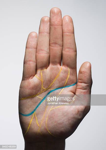 Hand with many yellow lines and a single blue