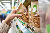 Hand with packaging of almond nuts in store