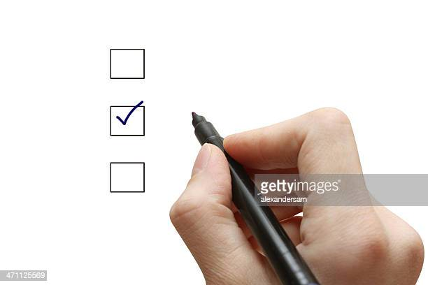 Hand with pen selecting one of three choices with tick