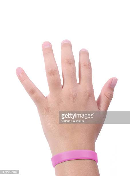 手にピンクのリストバンド - ゴム ストックフォトと画像