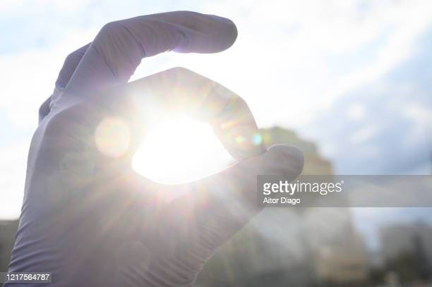 hand with protection globes against the sun doing ok sign. berlin. germany. - recovery stock pictures, royalty-free photos & images