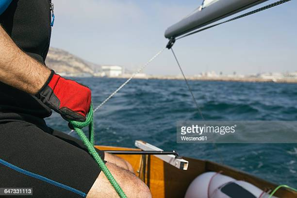 Hand with red glove of a man holding a rope and sailing with his sailboat at sea