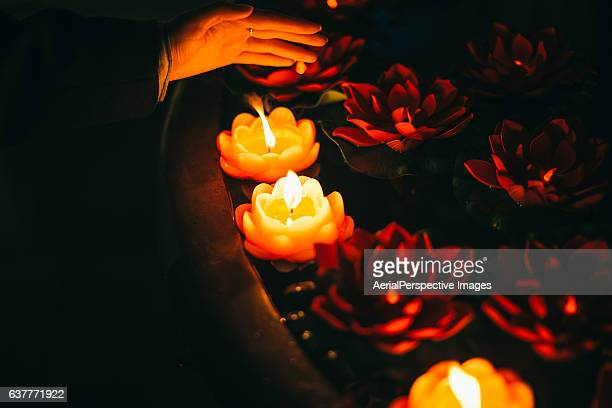 Hand with Red lotus-shaped candles burning in temple, Nanjing, China.