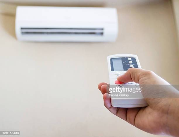 Hand with remote control air conditioner
