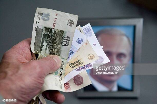 Hand with russian ruble banknotes and a framed Putin photo in the background on December 02 2014 in Bonn Germany