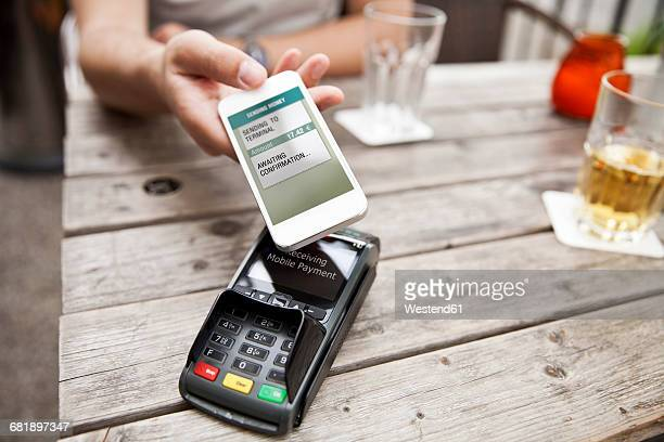 Hand with smart phone mobile paying at a cafe
