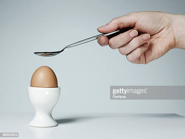 Hand with spoon and soft-boiled egg