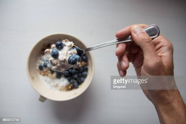 Hand with spoon full of cereal point of view from man eating breakfast