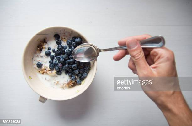 Hand with spoon reaching for breakfast cereal with blueberries and milk