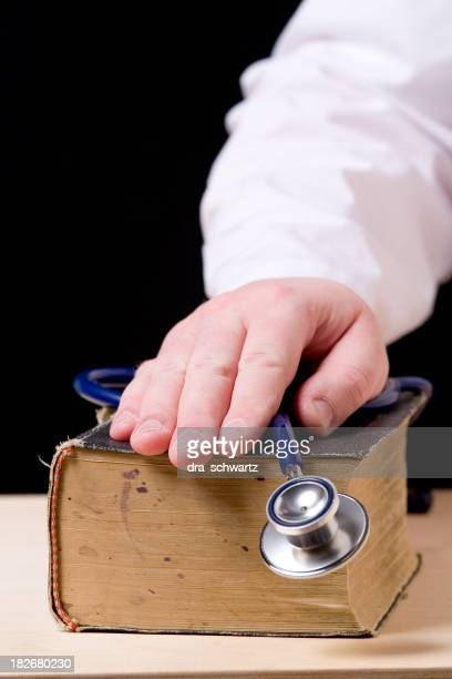 hand with stethoscope on top of old book