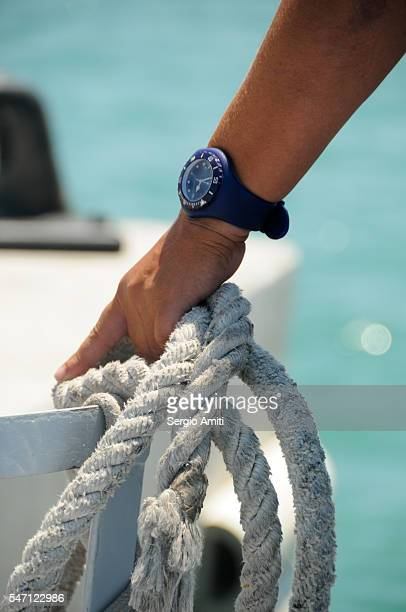 Hand with watch holding a rope on a boat with sea in the background