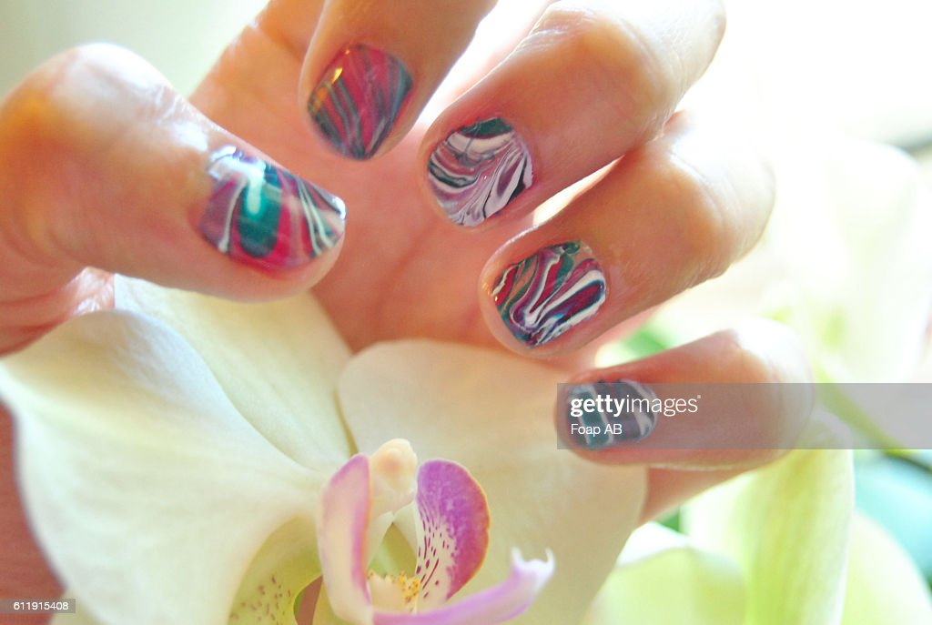 Hand With Water Marble Nail Art Holding Orchid Flower Stock Photo