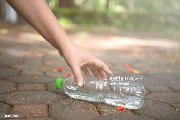 hand woman picking up plastic bottle cleaning in the public park. - picking up stock pictures, royalty-free photos & images