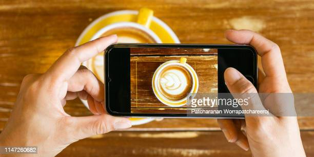 hand woman taking a picture of hot latte art coffee cup on wooden table with her smart phone sitting at a coffee shop. - hot women pics ストックフォトと画像