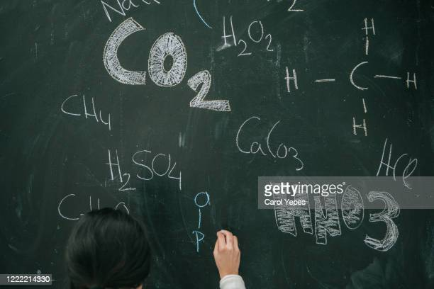 hand writes chemistry formulas through chalk on blackboard - chemical formula stock pictures, royalty-free photos & images