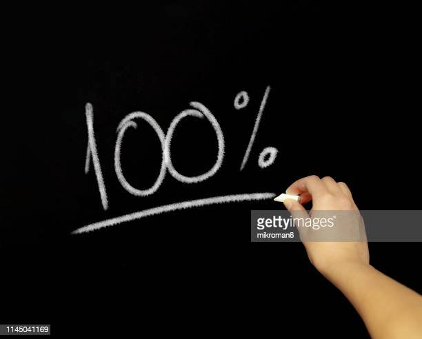 hand writing 100% with chalk in black board - percentage sign stock pictures, royalty-free photos & images