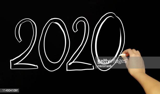hand writing 2020 new year with chalk in black board - 西暦2000年 ストックフォトと画像