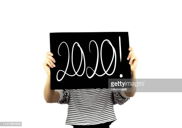 hand writing 2020 new year with chalk in black board - 2020 stock photos and pictures