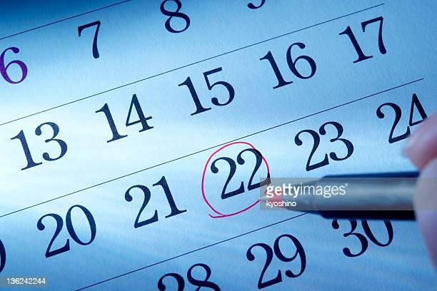 Main écrire une ronde rouge mark d'un calendrier
