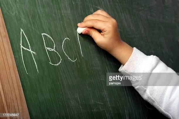 Hand writing ABC alphabet on blackboard
