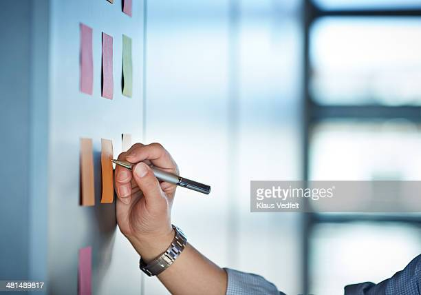 Hand writing on colorful Post-It notes on wall