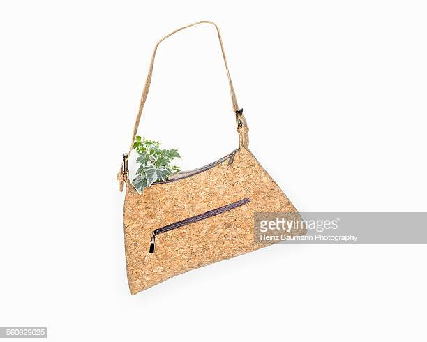 Handbag made of cork with ivy on white background.