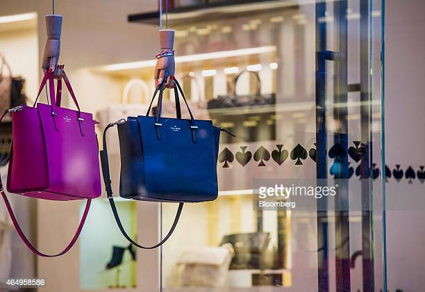Handbags hang on display in the window of a Kate Spade Co store in Corte Madera California US on Friday Feb 27 2015 Kate Spade Co is expected to...
