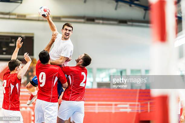 Handball player shooting at goal.