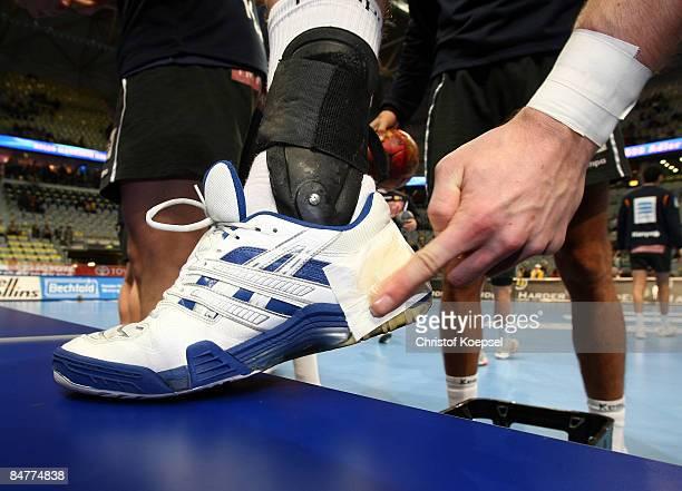 A handballer puts resin on his shoe before the Toyota Handball Bundesliga match between Rhein Neckar Loewen and Fuechse Berlin at the SAPArena on...