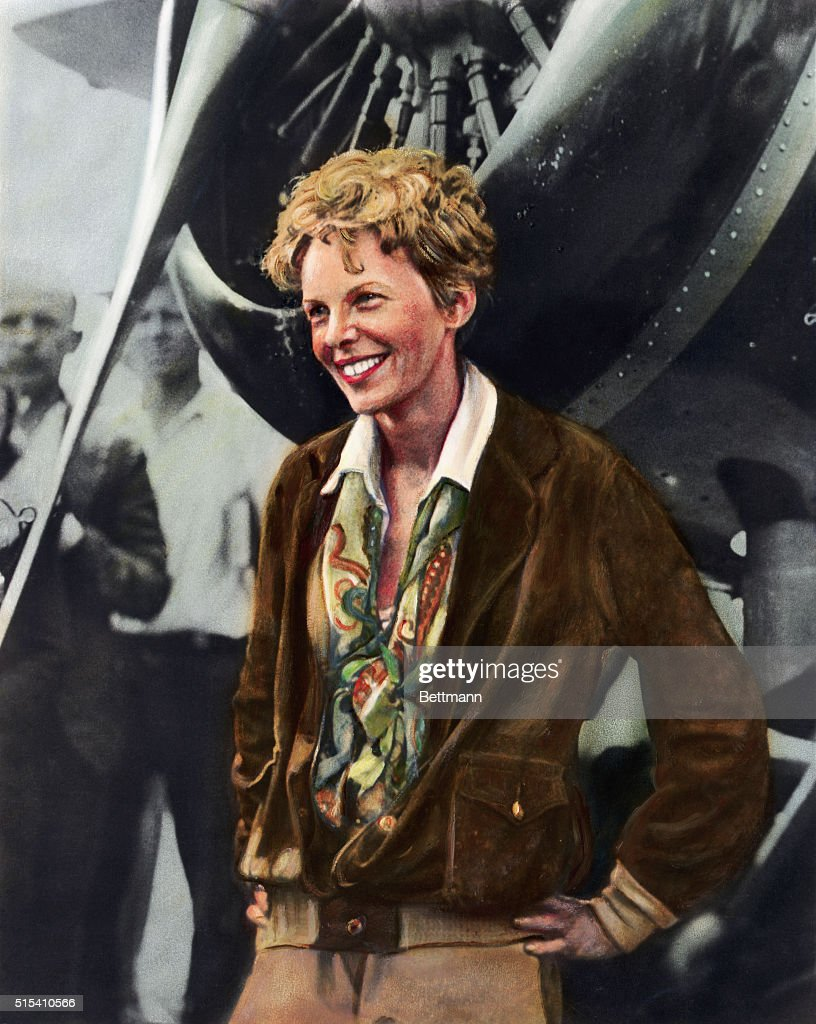 Hand-colored portrait of Amelia Earhart, (1898-1937), American aviator, smiling as she stands in front of her plane. Undated illustration.