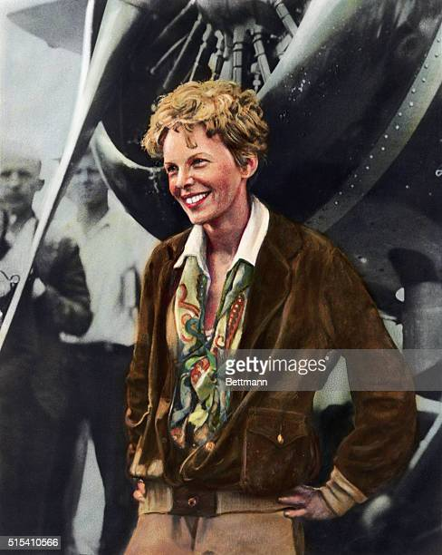 Handcolored portrait of Amelia Earhart American aviator smiling as she stands in front of her plane Undated illustration