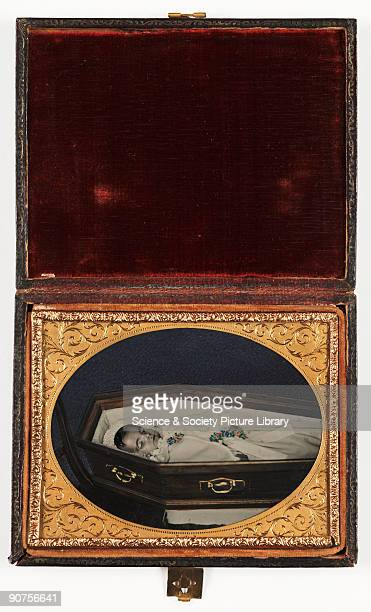 Handcoloured ambrotype photograph by an unknown photographer in red morocco case with oval gilt mat patterned pinchbeck frame and lacquered back