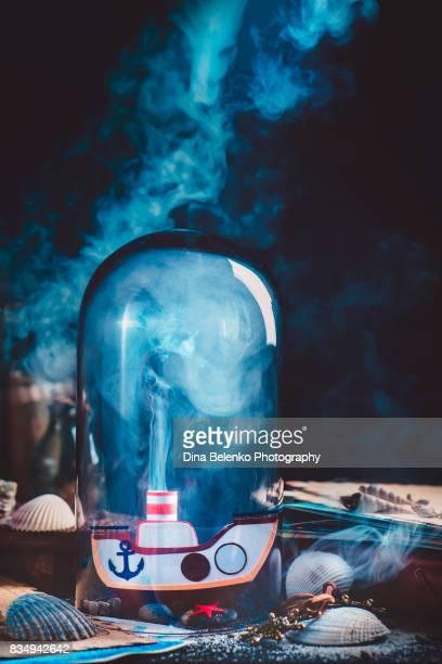 Handcrafted paper boat with steam under glass dome. Still life with captain workplace.