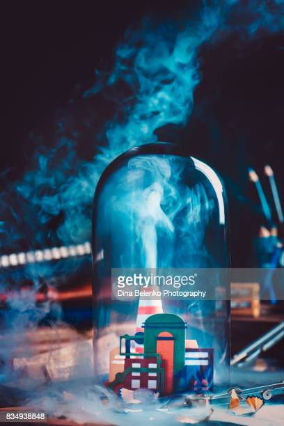 Handcrafted paper industrial plant with smoke under glass dome. Still life with blue collar workplace.