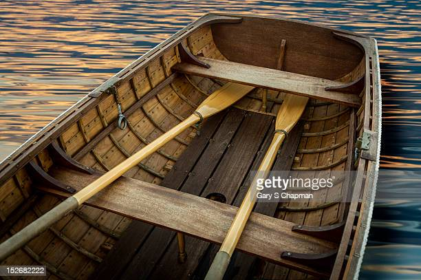 Handcrafted wooden rowboat with oars