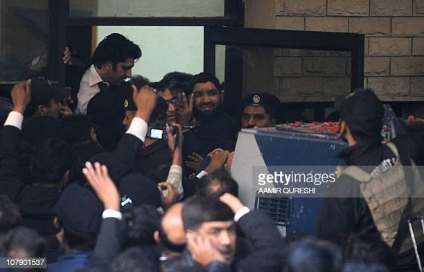 Handcuffed arrested Pakistani bodyguard Malik Mumtaz Hussain Qadri the alleged killer of Punjab's governor Salman Taseer makes a victory sign as he...