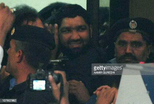 Handcuffed arrested Pakistani bodyguard Malik Mumtaz Hussain Qadri the alleged killer of Punjab's governor Salman Taseer smiles as he leaves the an...