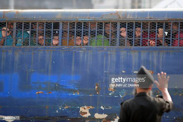 Handcuffed Bangladesh Rifles soldiers look through a prison van as they arrive at the special court in Dhaka on November 5 2013 Some 800 Bangladeshi...