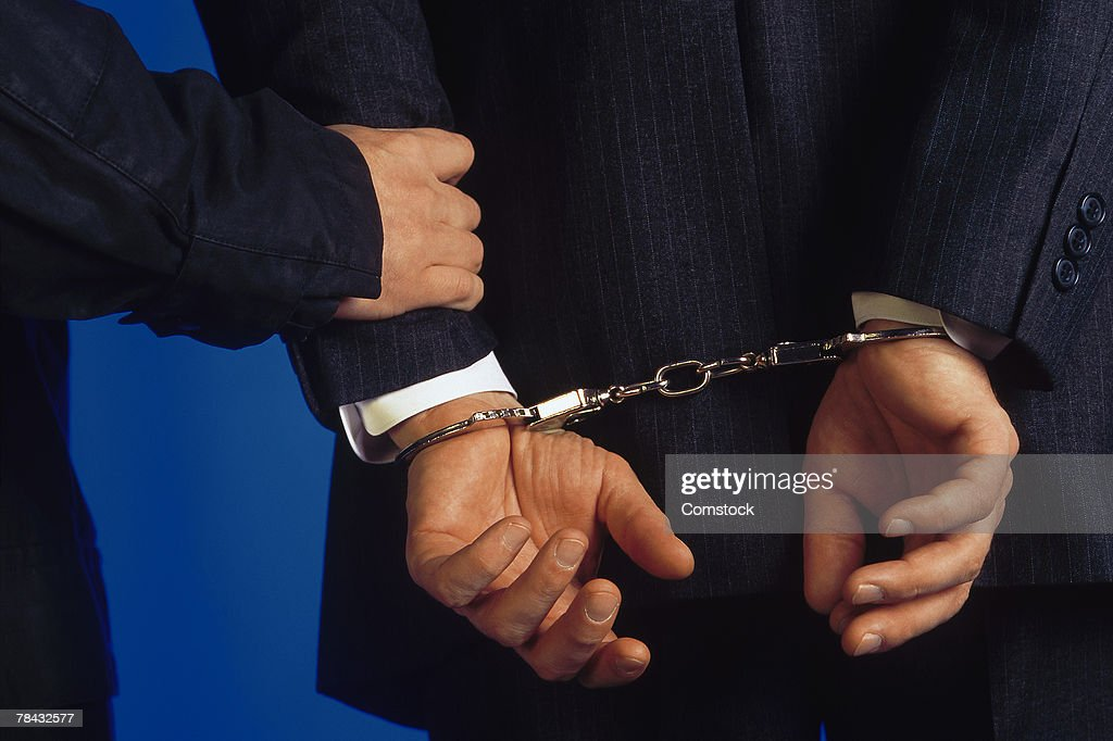 Handcuffed businessman being escorted by officer : Stock Photo