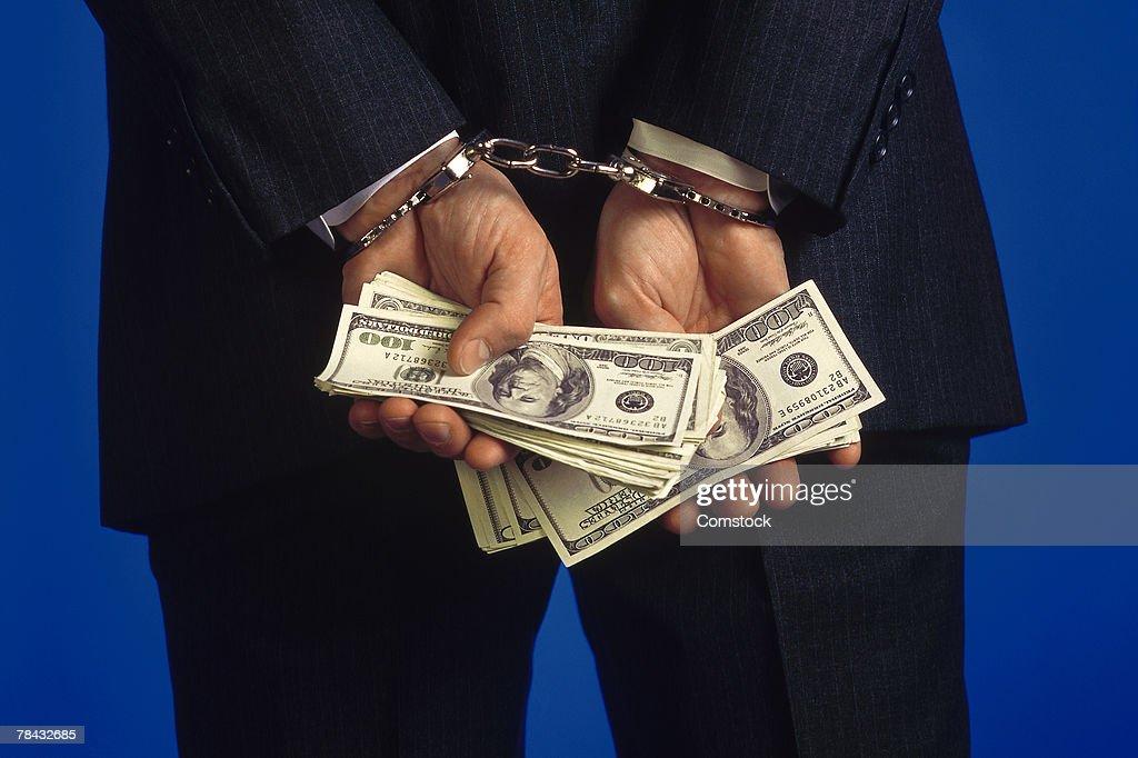 Handcuffed businessman holding cash : Stockfoto
